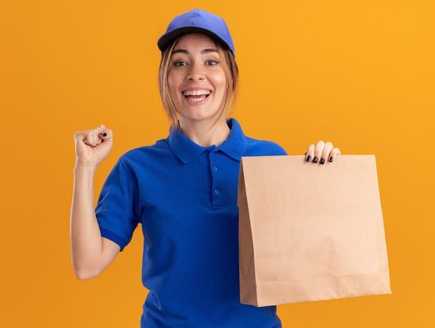 制服を着たうれしそうな若いかわいい配達の女の子は拳を保ち、オレンジ色の紙のパッケージを保持します