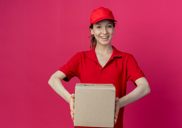 Joyful young pretty delivery girl in red uniform and cap holding carton box isolated on crimson background with copy space