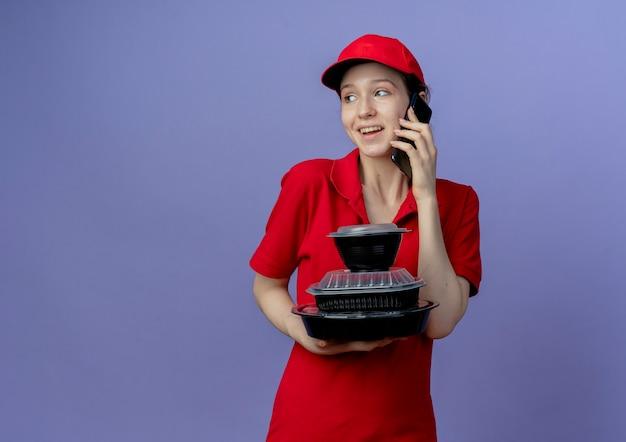 Радостная молодая симпатичная доставщица в красной форме и кепке смотрит в сторону, держащую контейнеры для еды и разговаривает по телефону, изолированном на фиолетовом фоне с копией пространства