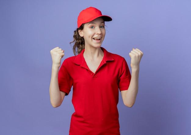 Gioiosa giovane ragazza graziosa di consegna che indossa l'uniforme rossa e cappuccio facendo sì gesto isolato su sfondo viola con spazio di copia