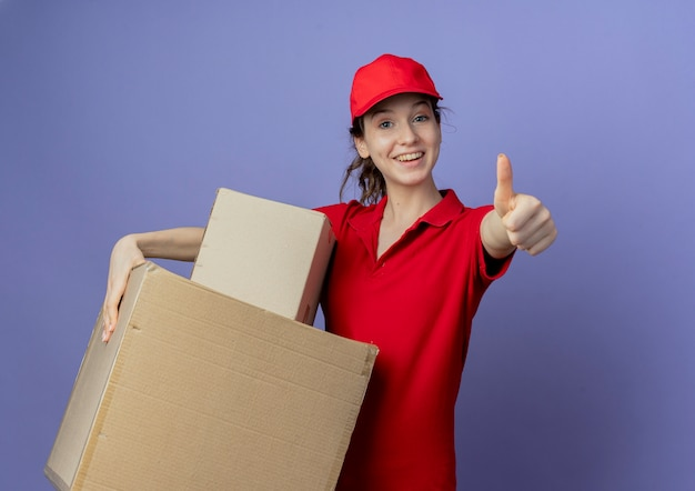 Joyful young pretty delivery girl wearing red uniform and cap holding carton boxes and showing thumb up at camera isolated on purple background with copy space