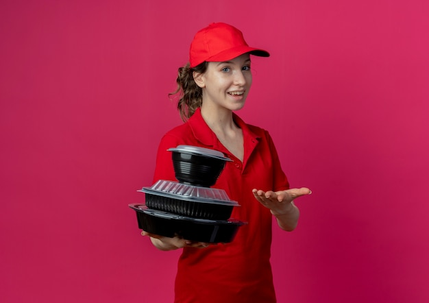 Joyful young pretty delivery girl wearing red uniform and cap holding and pointing with hand at food containers