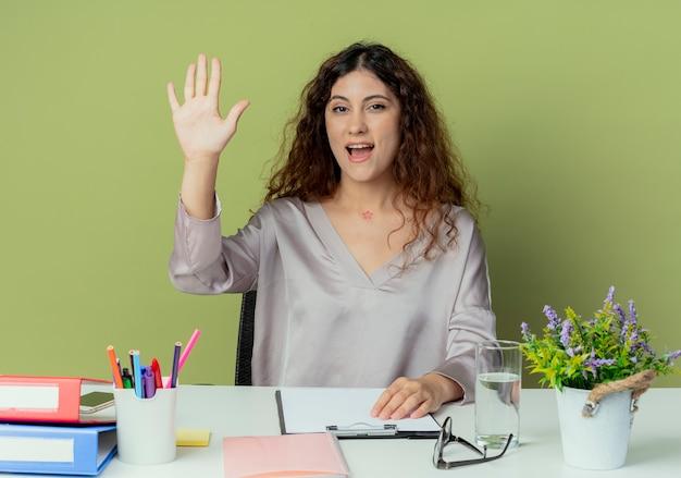 オリーブの背景に分離されたこんにちはジェスチャーを示すオフィスツールと机に座ってうれしそうな若いきれいな女性のサラリーマン
