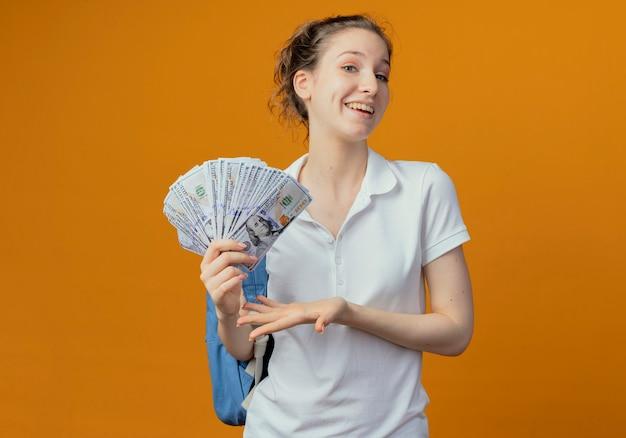 Радостная молодая симпатичная студентка в задней сумке держит и показывает рукой на деньги
