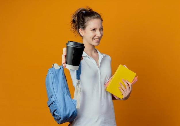 Радостная молодая симпатичная студентка в задней сумке держит ручку блокнота с книгой, подмигивая и протягивая пластиковую кофейную чашку