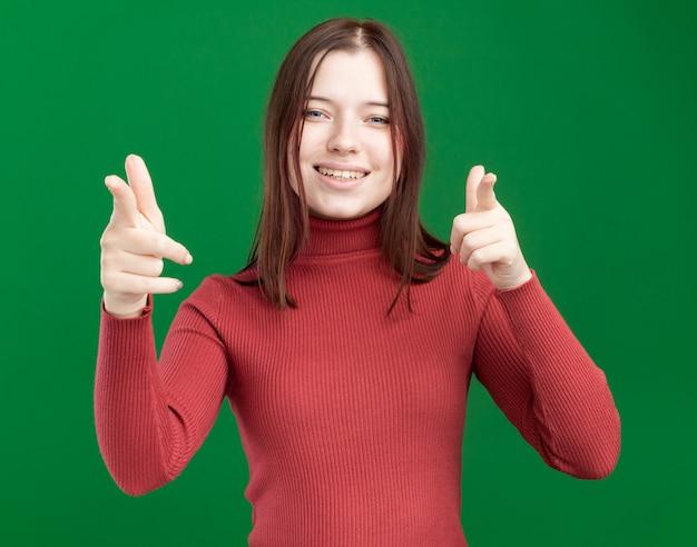 Giovane ragazza graziosa allegra che ti fa gesto isolato sulla parete verde