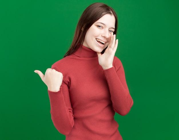 コピースペースと緑の壁に隔離された口の近くに手を置いて横を指しているうれしそうな若いかわいい女の子