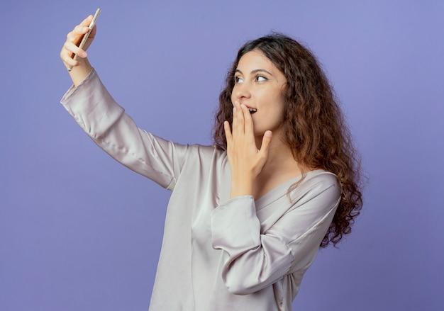 うれしそうな若いかわいい女の子が自分撮りを取り、青い壁に隔離された手で口を覆った