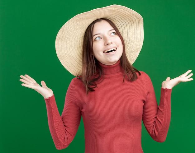 Gioiosa giovane bella ragazza che indossa un cappello da spiaggia che guarda in alto mostrando le mani vuote