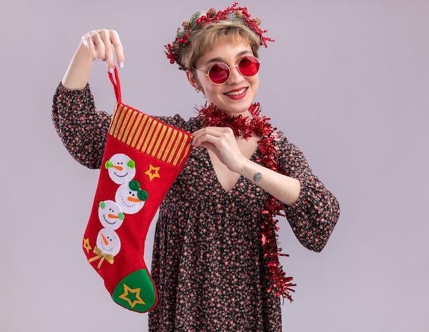 白い背景で隔離のカメラを見てクリスマスの靴下を保持しているメガネと首の周りにクリスマスのヘッドリースと見掛け倒しの花輪を身に着けているうれしそうな若いかわいい女の子