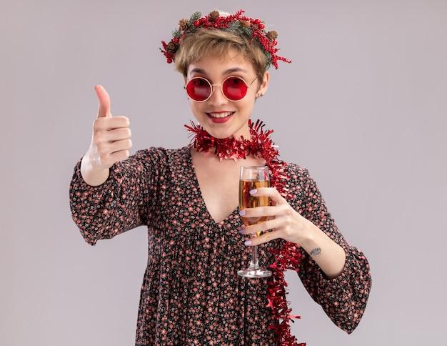 クリスマスの頭の花輪と首の周りに見掛け倒しの花輪を身に着けているうれしそうな若いかわいい女の子は、白い背景で隔離の親指を示すカメラを見てシャンパンのガラスを保持しているメガネ