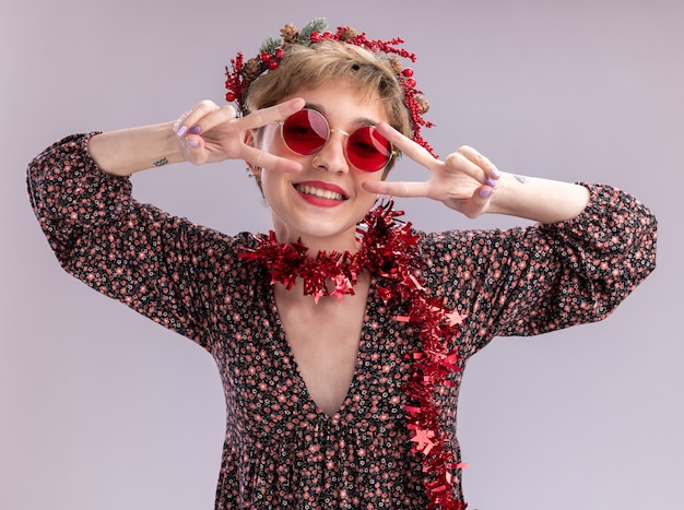 흰색 배경에 고립 된 눈 근처 v 기호 기호를 보여주는 카메라를보고 안경 목에 크리스마스 머리 화 환과 반짝이 갈 랜드를 입고 즐거운 젊은 예쁜 여자
