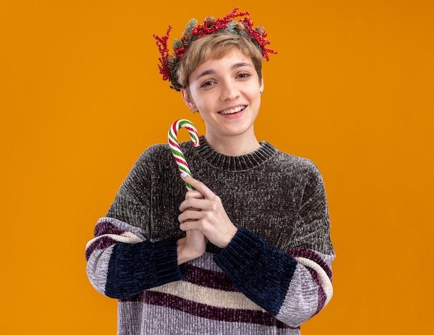 オレンジ色の背景に分離されたカメラを見てクリスマスの甘い杖を保持しているクリスマスの頭の花輪を身に着けているうれしそうな若いかわいい女の子