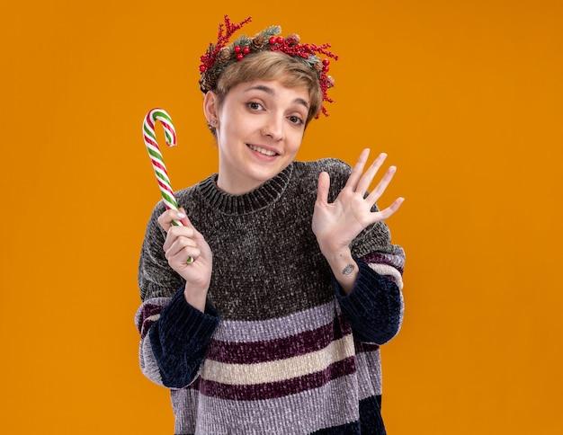 オレンジ色の背景で隔離の空の手を示すカメラを見てクリスマスの甘い杖を保持しているクリスマスのヘッドリースを身に着けているうれしそうな若いかわいい女の子