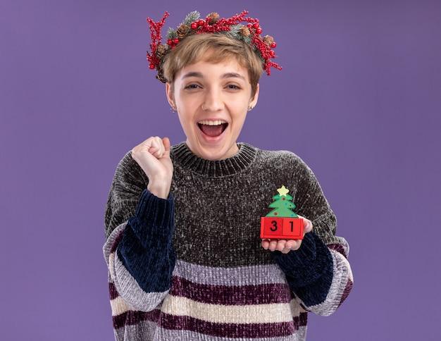 Радостная молодая красивая девушка в рождественском венке головы держит елочную игрушку с датой, глядя в камеру, делая жест да, изолированные на фиолетовом фоне