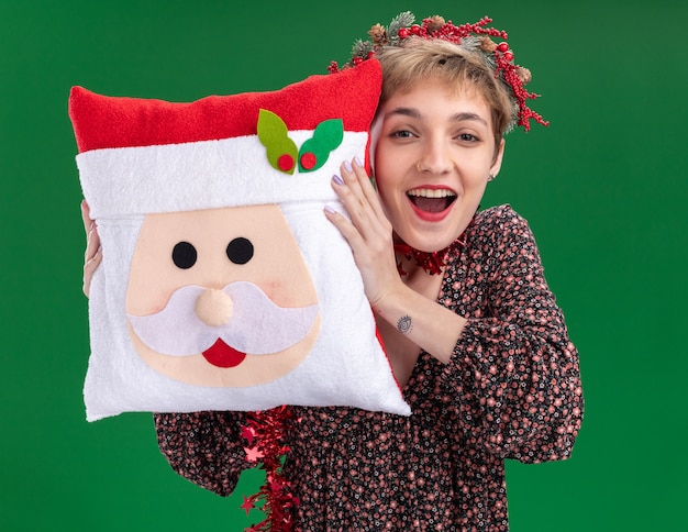 Joyful young pretty girl wearing christmas head wreath and tinsel garland around neck holding santa claus pillow touching head with it looking at camera isolated on green background