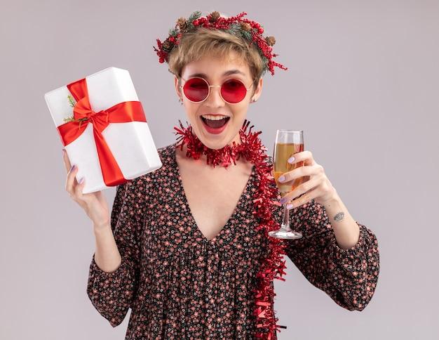 Gioiosa giovane bella ragazza che indossa la corona della testa di natale e la ghirlanda di orpelli intorno al collo con gli occhiali che tengono il pacchetto regalo e un bicchiere di champagne che guarda l'obbiettivo ammiccante isolato su priorità bassa bianca