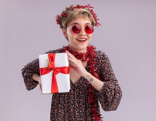 Gioiosa giovane bella ragazza che indossa la testa di natale ghirlanda e orpello ghirlanda intorno al collo con gli occhiali tenendo il pacchetto regalo guardando la telecamera isolata su sfondo bianco