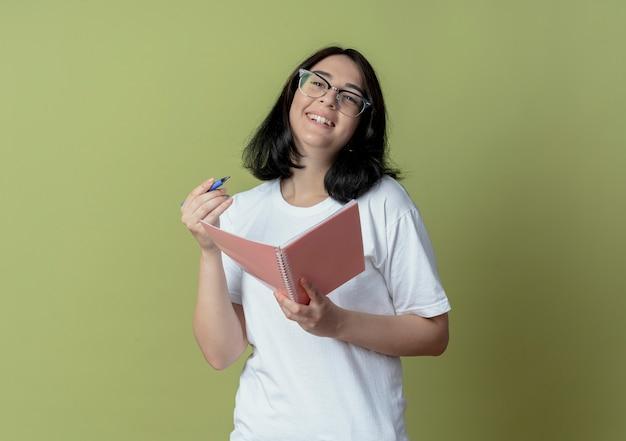 まっすぐに見えるペンとメモ帳を保持している眼鏡をかけているうれしそうな若いかわいい女の子