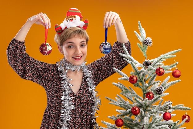 Радостная молодая красивая девушка в ободке санта-клауса и гирлянде из мишуры на шее стоит возле украшенной елки, держа рождественскую безделушку возле головы, изолированную на оранжевой стене