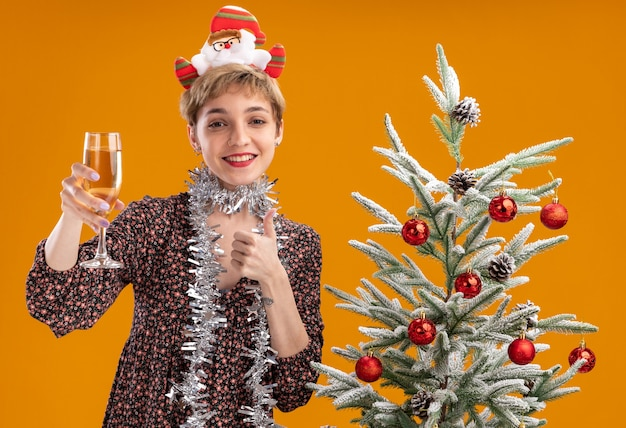 Joyful young pretty girl wearing santa claus headband and tinsel garland around neck standing near decorated christmas tree holding glass of champagne  showing thumb up isolated on orange wall