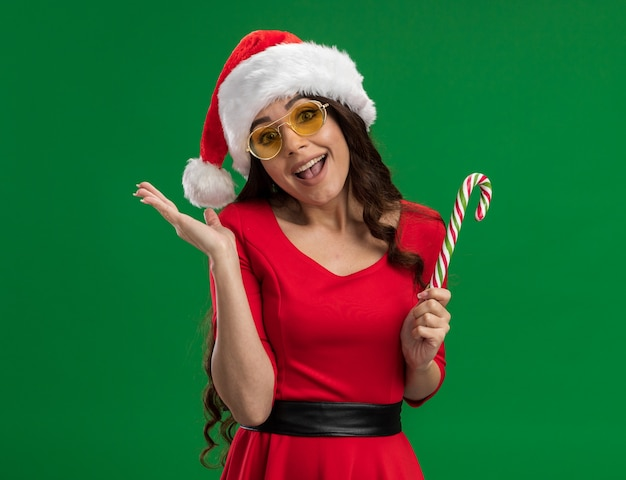 Радостная молодая красивая девушка в шляпе санта-клауса и очках держит рождественскую конфету, глядя в камеру, показывая пустую руку, изолированную на зеленом фоне