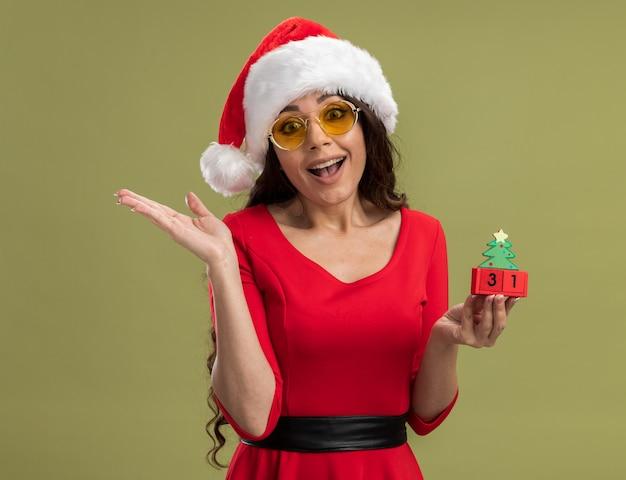 Радостная молодая красивая девушка в шляпе санта-клауса и очках держит елочную игрушку с датой, глядя показывая пустую руку