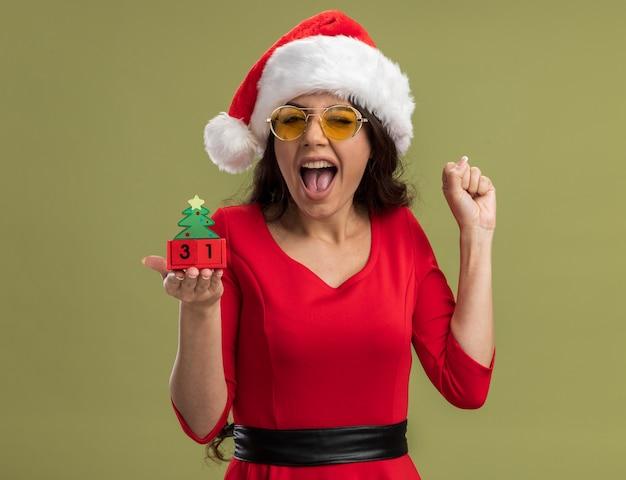 サンタの帽子とメガネを身に着けているうれしそうな若いかわいい女の子は、オリーブグリーンの背景に分離されたはいジェスチャーを行うカメラを見て日付ウィンクとクリスマスツリーのおもちゃを保持 無料写真