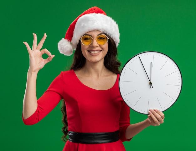 Радостная молодая красивая девушка в шляпе санта-клауса и очках держит часы, глядя в камеру, делает хорошо, знак, изолированные на зеленом фоне