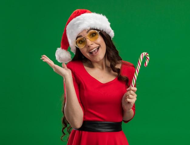 Gioiosa giovane ragazza graziosa che indossa il cappello della santa e bicchieri tenendo il bastoncino di zucchero di natale guardando la telecamera mostrando la mano vuota isolata su sfondo verde