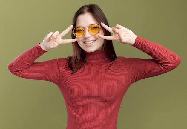 눈 근처에 v 기호 기호를 보여주는 선글라스를 착용하는 즐거운 젊은 예쁜 여자