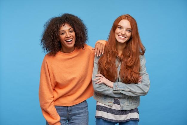 파란색 벽 위에 포즈를 취하는 동안 넓게 웃고 행복하게 보면서 그들의 하얀 완벽한 이빨을 보여주는 즐거운 젊은 예쁜 여자 친구