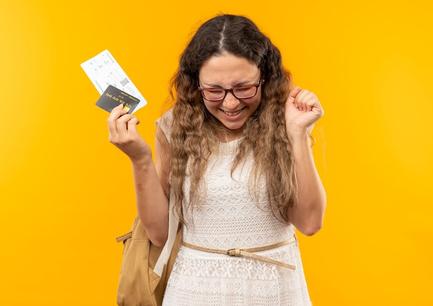 Joyful young pretty schoolgirl wearing glasses and back bag holding airplane tickets and credit card clenching fist with closed eyes isolated on yellow