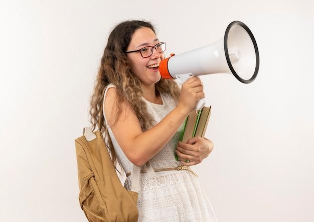 Gioiosa giovane studentessa graziosa con gli occhiali e borsa posteriore in possesso di libri parlando da altoparlante isolato su bianco