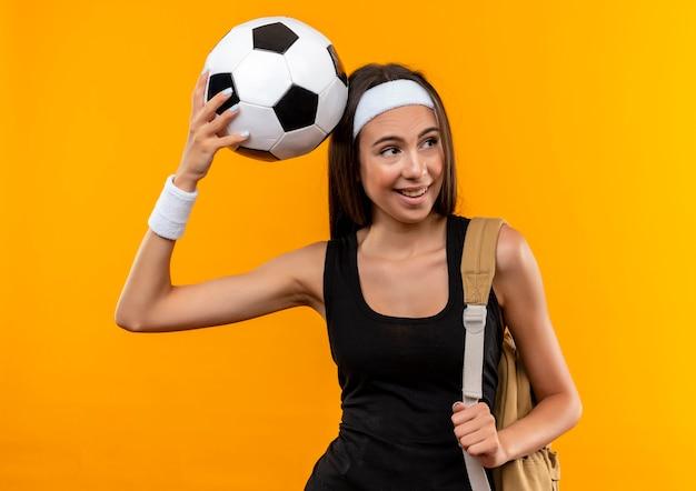 オレンジ色のスペースで隔離された側を見て頭にサッカーボールを置くヘッドバンドとリストバンドとバックバッグを身に着けているうれしそうな若いかなりスポーティーな女の子