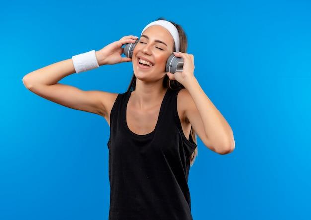Радостная молодая симпатичная спортивная девушка в головной повязке, браслете и наушниках слушает музыку с закрытыми глазами на синем пространстве