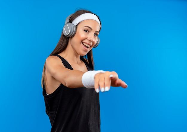 ヘッドバンドとリストバンドと青いスペースで隔離の手を伸ばしてヘッドフォンを身に着けているうれしそうな若いかなりスポーティーな女の子