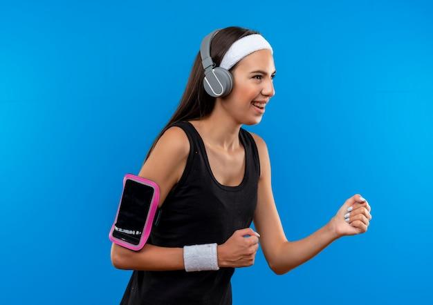 ヘッドバンドとリストバンドとヘッドフォンを身に着けているうれしそうな若いかなりスポーティーな女の子は、青い空間で隔離された側を見て縦断ビューで立っている電話の腕章を持っています
