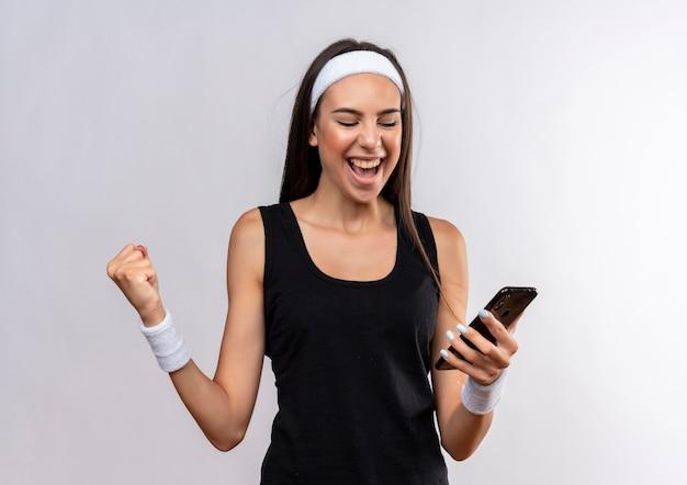 ヘッドバンドとリストバンドを身に着けて携帯電話を持って見て、白いスペースで拳を握りしめているうれしそうな若いかなりスポーティーな女の子