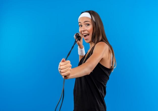 Радостная молодая симпатичная спортивная девушка с повязкой на голову и браслетом, держащей и вытягивающей скакалку, изолированную на синем пространстве