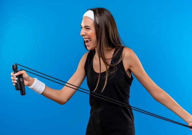 Радостная молодая симпатичная спортивная девушка с ободком и браслетом держит скакалку и смотрит в сторону, изолированную на синем пространстве