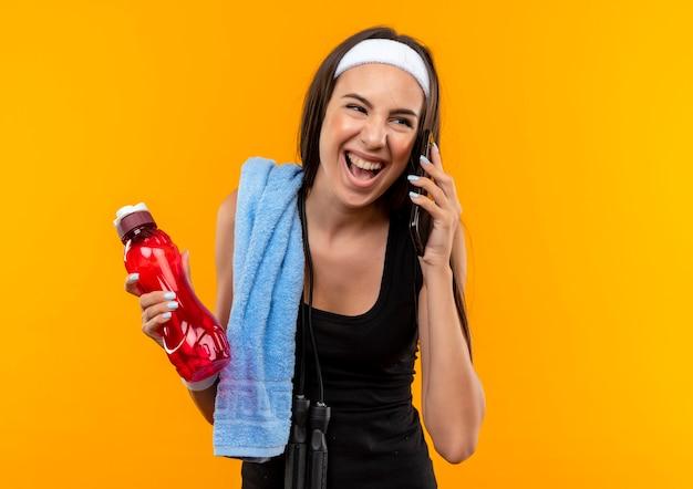 Радостная молодая симпатичная спортивная девушка с головной повязкой и браслетом, держащая бутылку с водой, разговаривает по телефону, глядя в сторону