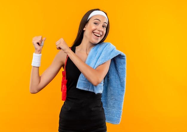 タオルでヘッドバンドとリストバンドを身に着けて、オレンジ色のスペースで後ろを指している彼女の肩に縄跳びをしているうれしそうな若いかなりスポーティーな女の子
