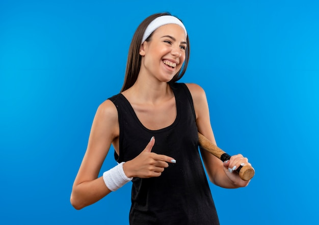 Joyful young pretty sporty girl wearing headband and wristband holding baseball bat looking and pointing at side isolated on blue space