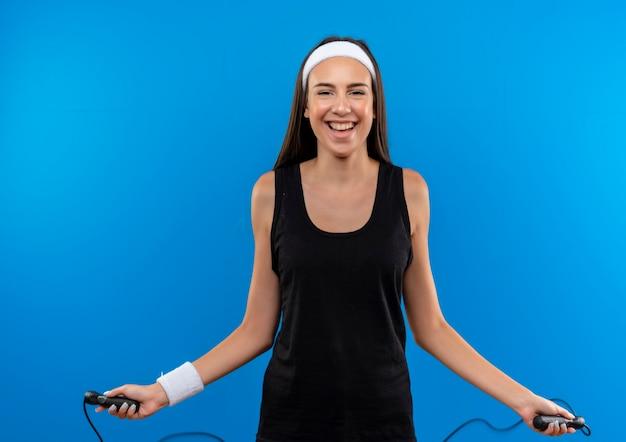 Gioiosa giovane ragazza abbastanza sportiva che indossa la fascia e la corda di salto del wristband isolata sullo spazio blu