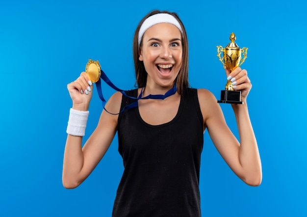 Joyful young pretty sporty girl wearing headband and wristband and medal around her neck holding winner cup and medal isolated on blue space