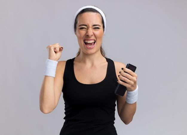 Gioiosa giovane ragazza abbastanza sportiva che indossa fascia e braccialetti che tengono il telefono cellulare facendo sì gesto isolato sul muro bianco con spazio copia