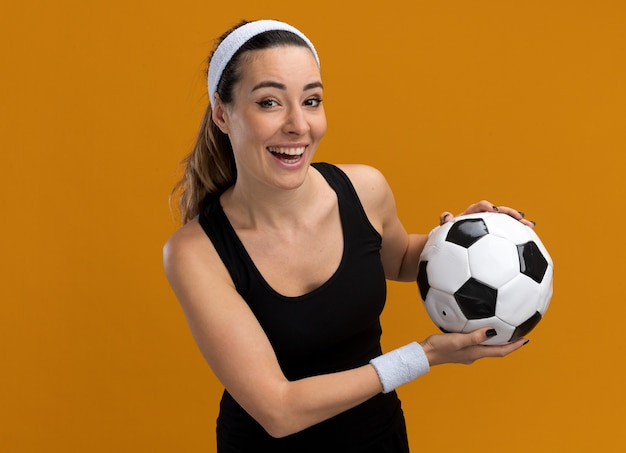 Joyful young pretty sporty girl wearing headband and wristbands holding soccer ball  isolated on orange wall with copy space