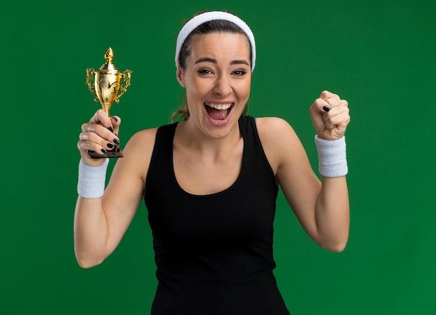 Gioiosa giovane ragazza abbastanza sportiva che indossa fascia e braccialetti che tengono la coppa del vincitore facendo sì gesto
