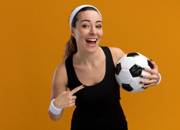 コピースペースでオレンジ色の壁に隔離された正面を見てそれを指しているサッカーボールを保持しているヘッドバンドとリストバンドを身に着けているうれしそうな若いかなりスポーティーな女性